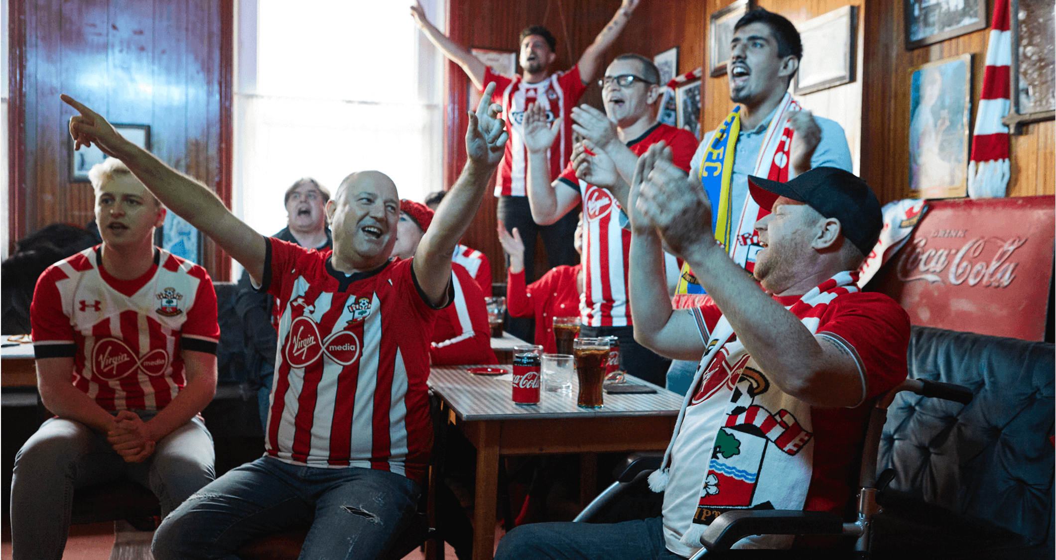 Group of Southampton fans cheer inside a pub with Coca Cola branding.