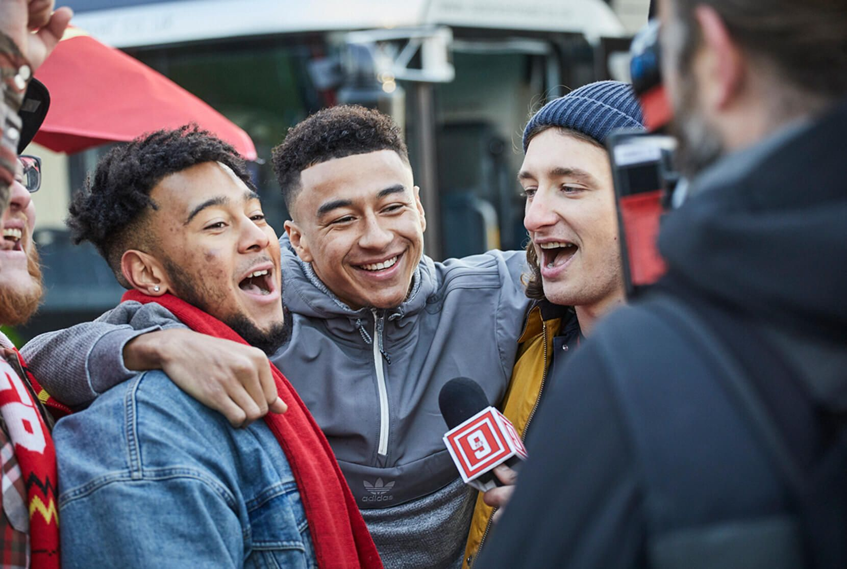 Jesse Lingard poses with two smiling fans