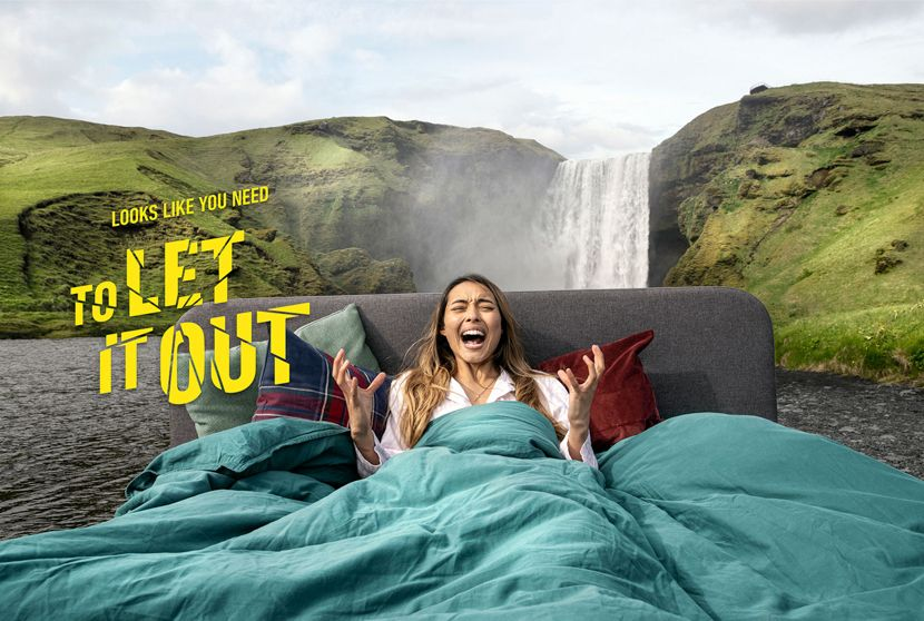 A woman screaming, lying on a bed in front of a volcanic waterfall. Text reads ' Looks Like You Need To Let it Out'