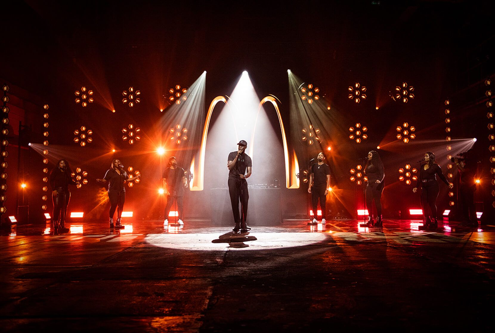 Stormzy sings in front of a large Mcdonalds logo on a dark stage with red uplighting