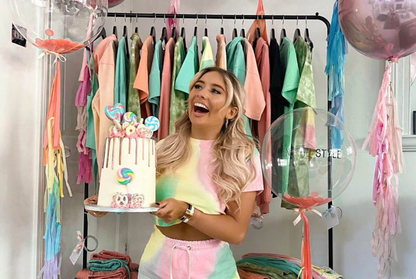 Influencer Saffron Barker laughs whilst holding a cake, in front of a clothing rail